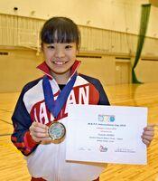 賞状とメダルを手にバトントワーリングの世界大会の優勝を喜ぶ久保柚葉さん