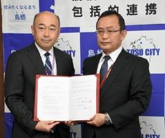 協定書を手にする橋本市長(左)と久米支部長=鳥栖市役所