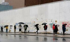 米ニューヨークのブルックリンで、大統領選の期日前投票のために距離をとりながら傘を差して列をつくる有権者=30日(AP=共同)