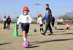 サガン鳥栖のアカデミーコーチからドリブルなどを学ぶ児童たち=みやき町の三根東小