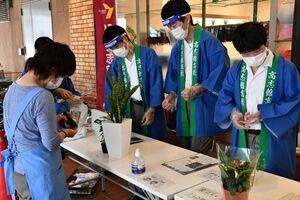 おそろいの法被を着て観葉植物などを販売する高志館高の生徒ら=佐賀市の佐賀玉屋南館前