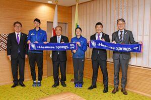 チームのタオルを広げて笑顔を見せる岩坂名奈選手(左から2番目)と戸江真奈選手(同4番目)。両選手の間は秀島敏行市長=佐賀市役所