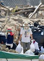 広島市安佐北区で土砂の撤去作業に当たるボランティア=23日午前