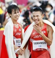 男子20キロ競歩で銀メダルを獲得し、銅メダルの山西利和(右)と笑顔で握手する池田向希=札幌市