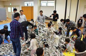 やぶった新聞を使って遊ぶ父親と子どもたち=神埼市の千代田町保健センター