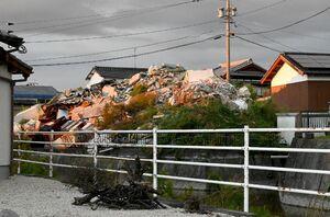 住宅地の一角に高く積まれたままの産業廃棄物。県の撤去命令などに応じなかったとして、神埼署は解体業の男を廃棄物処理法違反容疑で逮捕した=神埼市千代田町迎島