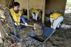 民家に流れ込んだ土砂を撤去するボランティア=17日午後、福岡県朝倉市