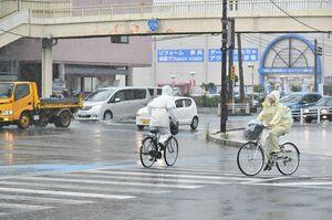 強い雨の中、雨具に身を包んで帰りを急ぐ高校生ら=9日夕、佐賀市の佐大南交差点