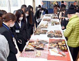 色とりどりのおせち料理を見つめる参加者たち=佐賀市神園の西九州大学短期大学部