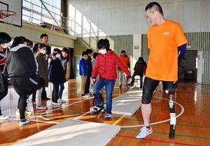 体験用の義足をはいた児童と、眞野雄輝選手=佐賀市の西与賀小学校