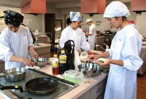 アサリや赤貝など有明海の二枚貝を使った創作料理に挑戦する参加者ら=佐賀市のアバンセ