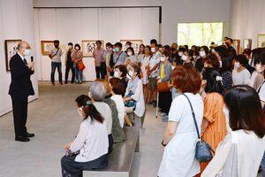 ギャラリートークで父の相田みつをを語る相田みつを美術館の相田一人館長(左)=佐賀市の佐賀県立美術館