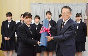 揮毫した作品を佐賀税務署の平山誠一郎署長に手渡す書道部の岸川瑠奈部長(左)