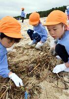 砂浜のごみ拾いをするリョーユー幼稚園の園児たち=唐津市の東の浜海岸