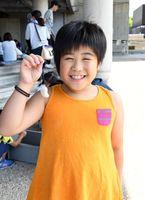 出来上がった勾玉(まがたま)を持ち、満面の笑みを見せる三日月小3年の貞含さん=佐賀市の県立博物館・県立美術館