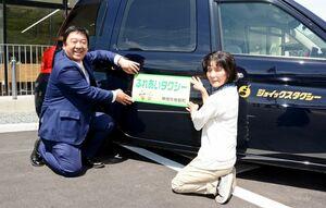 運行する車両に愛称を貼り付ける考案者の執行洋子さん(右)と運行するジョイックス交通の小山淳也代表取締役=神埼市脊振町の脊振交流センター