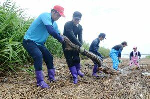 豪雨で下流に流れ着いた流木を引き揚げる漁業者ら=佐賀市川副町