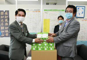 佐賀市教育委員会の東島正明教育長(左)に、マスクを渡すYLCの田中武志社長=佐賀市役所大財別館