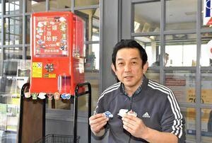 肥前吉田焼のマグネットが入ったカプセルトイ販売機と江口代表=嬉野市の肥前吉田焼窯元会館