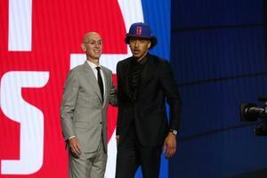 NBAドラフトでピストンズから全体1位で指名され、アダム・シルバー・コミッショナー(左)から祝福を受けるオクラホマ州立大のケイド・カニンガム=29日、ニューヨーク(USAトゥデー・ロイター=共同)