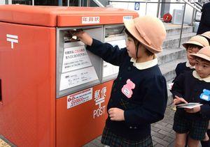 年賀はがきをポストに投函する園児=佐賀市の佐賀中央郵便局