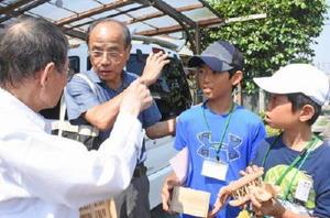 趣味の木工細工の話を熱心に聞く北川副小の児童=佐賀市の高齢者宅