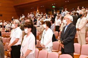 マスク姿で距離を取り、国歌斉唱する入学生たち=佐賀市の佐賀市文化会館