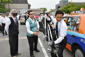 妊婦ジャケットや子どもの視界を疑似体験できるゴーグルを身に着け、子育て世代への対応を学ぶタクシー運転手=神埼市中央公民館