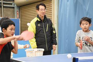 子どもたちを指導する岡本篤郎さん(中央)=鳥栖市桜町の鳥栖卓球センター