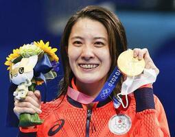 女子400メートル個人メドレーで優勝し、金メダルを手に笑顔の大橋悠依=東京アクアティクスセンター