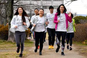 おそろいのTシャツを着て笑顔で走る荒木優佳さん(右)=佐賀市のどんどんどんの森