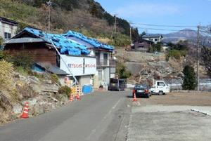 現在も屋根をビニールシートで覆った家や折れ曲がった電柱、崩れたのり面など地震の爪痕が生々しく残る被災地=熊本県阿蘇郡南阿蘇村立野地区