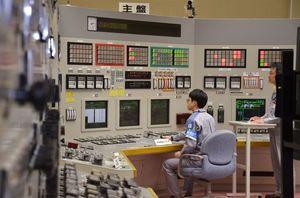 中央制御室のシミュレーターでレバーを操作し、制御棒を徐々に引き抜く作業を実演するオペレーター=東松浦郡玄海町