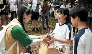 ゴール地点で記念品の交換をする西帰浦市の生徒(左)と海青中の生徒=唐津市鎮西町の波戸岬キャンプ場