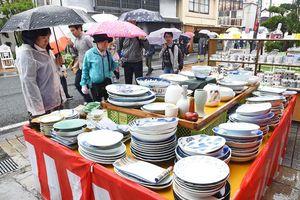小雨が降る中、露店に並べられた焼き物からお気に入りの品を探す陶器市客=29日、西松浦郡有田町