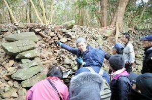 発掘調査が進む島津義弘陣跡の主郭南面の石垣を見つめる説明会の参加者たち=唐津市鎮西町