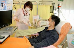 盛岡市で献血する男性。新型コロナの影響で献血者数の減少が懸念され、日赤は広く協力を呼び掛けている=7月31日