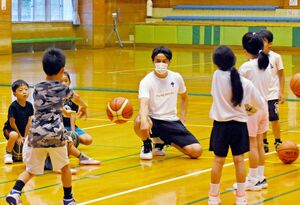 参加者のパスを見守る佐賀バルーナーズの水町亮介アカデミーコーチ(中央)=佐賀市立体育館