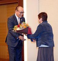就任を祝う花束を受け取るJA佐賀中央会の金原壽秀会長(左)=佐賀市のホテルマリターレ創世