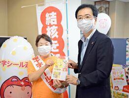 大川内直人健康福祉部長に結核予防グッズなどを渡し、活動への協力を呼びかけた山口七重会長(左)=県庁