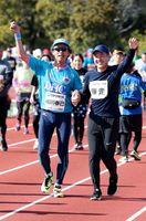 ゴール前で声援に応えるゲストランナーの栁川春己さん(左)=県総合運動場補助競技場