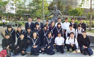 ブルースリーの像の前で記念撮影する生徒たち