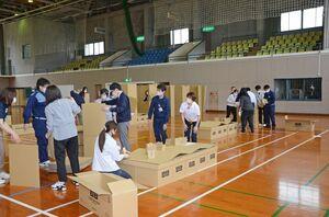 改良された段ボールベッドを組み立てる職員=武雄市の白岩体育館