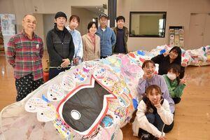 巨大こいのぼりを作った天山ものづくり塾のメンバーと、古賀百葉さん(手前右)ら西九州大生たち=小城市のゆめぷらっと小城