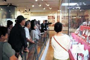 鈴田由紀夫館長の案内でヨーロッパに輸出された有田焼などを見学する参加者=有田町の県立九州陶磁文化館