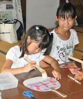 染め和紙でうちわ作りをする子どもたち=佐賀市の旧三省銀行