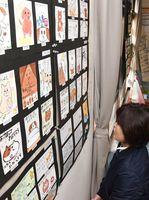 郵便局を利用する人たちが、千代田中の生徒たちが描いた作品を眺めている=神埼市千代田町の千歳郵便局