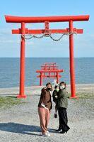 潮が満ち、海中に漬かった鳥居を前に写真を撮る人々=太良町の大魚神社(撮影・志垣直哉)