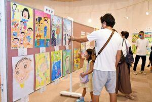 家族の思い出や日常風景を描いた作品に見入る親子連れ=佐賀新聞ギャラリー