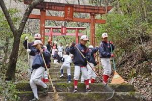 神社に通じる石段の落ち葉をほうきで取り除く子どもたち=佐賀市金立町の正現稲荷神社参道